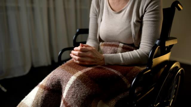 Movilidad-nerviosa-mujer-apretón-de-manos-sintiéndose-solo-y-desamparado-silla-de-ruedas
