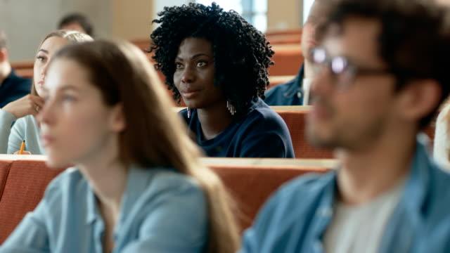 Große-Gruppe-von-Multi-ethnischen-Studenten-hören-einen-Vortrag-im-Klassenzimmer-Helle-Jugendliche-Studie-an-der-Universität-