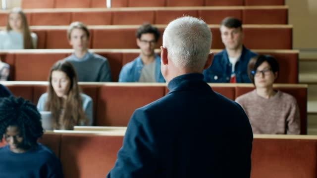 Kamera-mit-Klasse:-Prominente-Professor-schreiben-an-der-Tafel-und-Vortrag-zu-einem-Klassenraum-voller-Multi-ethnischen-Studenten-Moderne-Universität-mit-hellen-jungen-Leuten-im-Hörsaal-