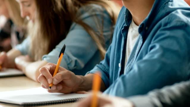 Primer-plano-de-la-fila-de-estudiantes-escribir-en-los-cuadernos-examen-Enfoque-de-las-manos-con-plumas-