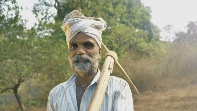 Un-hombre-con-barba-en-su-tierra-agrícola-rodeado-de-árboles-con-azada-