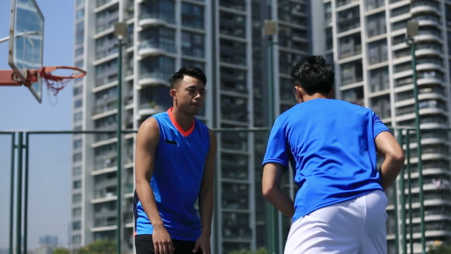 asian-young-adults-playing-basketball-on-outdoor-court