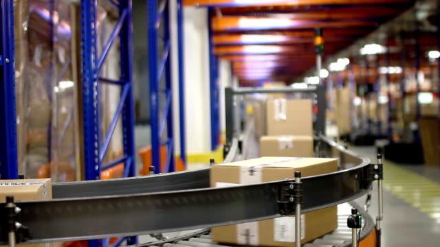 Cajas-de-cartón-en-cinta-transportadora-dentro-de-almacén
