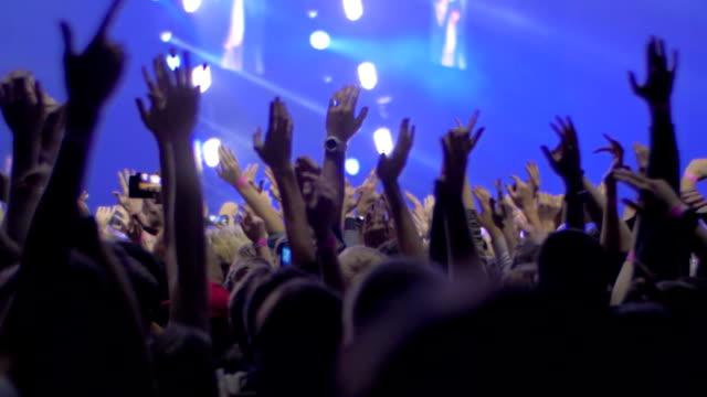 Personas-con-las-manos-para-arriba-en-el-concierto-de-rock-ve-con-las-luces-del-escenario
