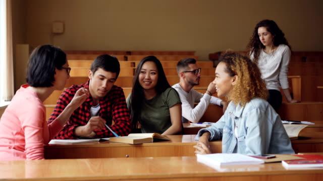 Sorglose-Mädchen-und-jungen-reden-und-lachen-sitzen-am-Schreibtisch-im-Hörsaal-Studenten-sind-entspannend-während-der-Pause-Gespräch-moderne-Bildung-und-Jugendkonzept-