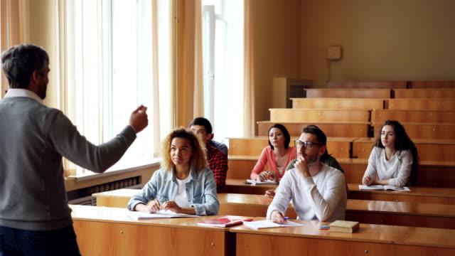 Grupo-multiétnico-de-jóvenes-es-escuchar-al-maestro-y-sonriendo-levantando-manos-profesor-es-apuntando-a-la-chica-y-hablar-con-ella-Concepto-de-alumnos-y-tutores-