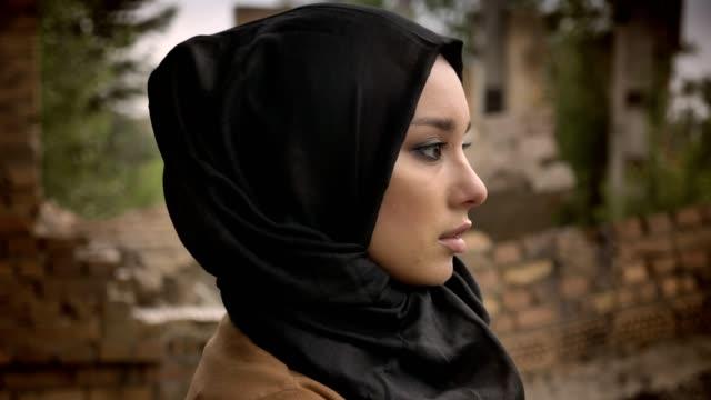 Joven-musulmana-hijab-mirando-lejos-y-al-cámara-preocupada-y-con-miedo-arruinado-edificio-de-fondo