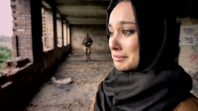 Young-sad-muslim-woman-in-hijab-crying-when-armed-soldier-going-towards-woman-abandoned-building-war-concept