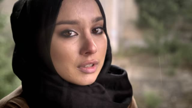 Portrait-of-young-muslim-woman-in-hijab-looking-at-camera-with-sad-depressed-expression-during-rain