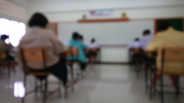 Detrás-de-estudiantes-universitarios-del-grupo-de-las-niñas-la-prueba-del-examen-en-sala-y-estudiante-sentado-en-silla-de-la-fila-haciendo-exámenes-finales-en-el-aula-con-el-uniforme-de-Tailandia-Concepto-de-Educación-de-Asia-Vista-superior-