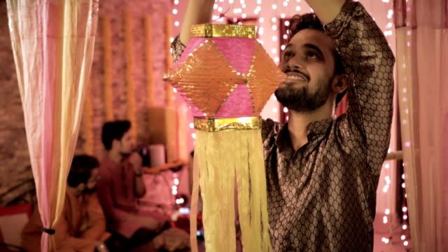 -Un-varón-joven-con-kurta-colgantes-coloridos-Diwali-Kandil-mientras-sus-colegas-sentado-y-hablando-en-el-fondo