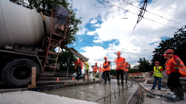 Concrete-works-for-road-maintenance-construction-with-many-workers-and-mixer-timelapse-hyperlapse