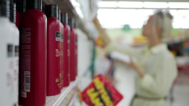 Blurred-young-woman-choosing-hair-conditioner-or-shampoo-in-a-beauty-shop-Woman-holding-a-body-care-product
