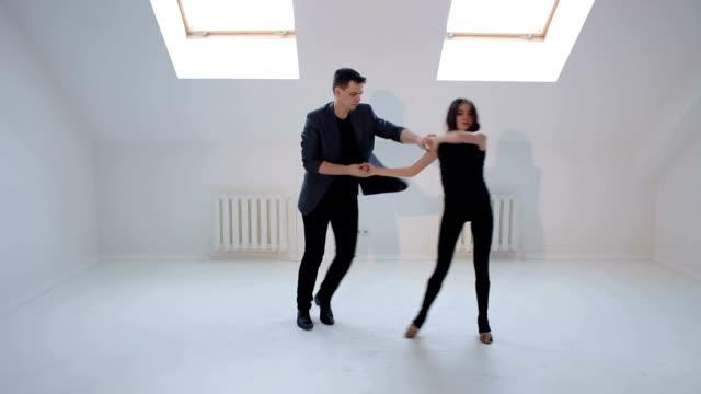 Flexibles-bailarines-bailan-bailes-de-salón-de-baile-en-un-luminoso-comedor-con-ventanas-pequeñas-