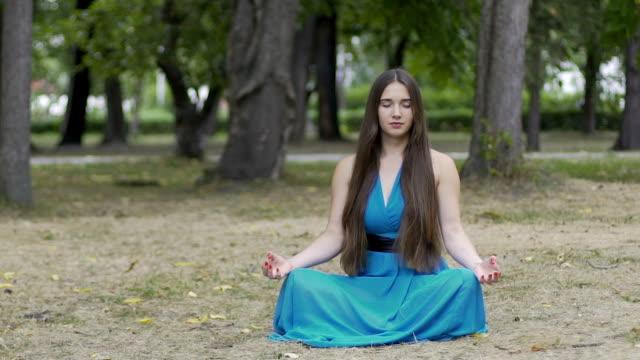 Dolly-Schuss-von-Meditierenden-Frau-im-Park-schöne-langhaarige-weiblichen-inneren-Frieden
