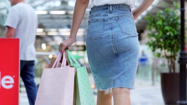 Rückansicht-des-eleganten-jungen-Frau-in-Denim-Bleistiftrock-zu-Fuß-im-Einkaufszentrum-in-Richtung-Rolltreppe-mit-bunten-Taschen-in-der-Hand-nach-dem-erfolgreichen-Einkauf-Verkauf