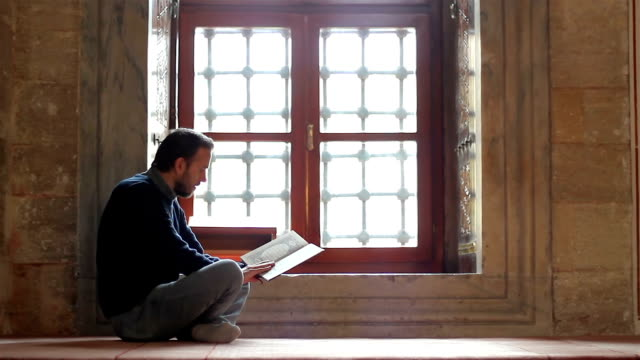 Young-muslim-reading-holy-book-(qoran)-in-mosque