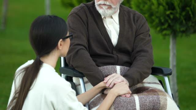 Hija-bondadoso-apoyo-a-padre-en-silla-de-ruedas-durante-la-rehabilitación