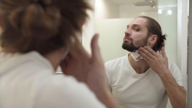 Man-Applying-Shaving-Foam-On-Face-Skin-And-Looking-In-Mirror