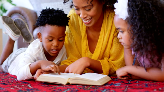 Front-view-of-black-mother-with-her-children-reading-a-book-in-a-comfortable-home-4k