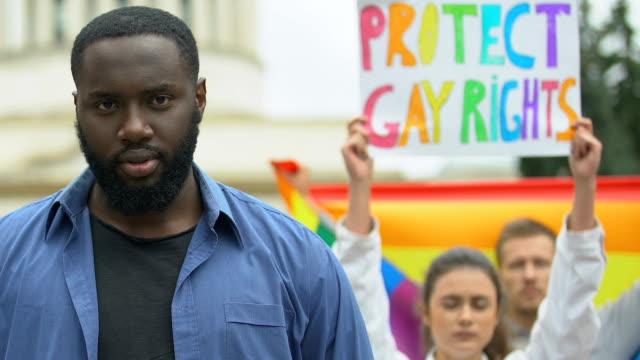 Schwarzer-Mann-hebt-Regenbogenherz-zusammen-mit-Demonstranten-für-LGBT-Rechte-Kundgebung