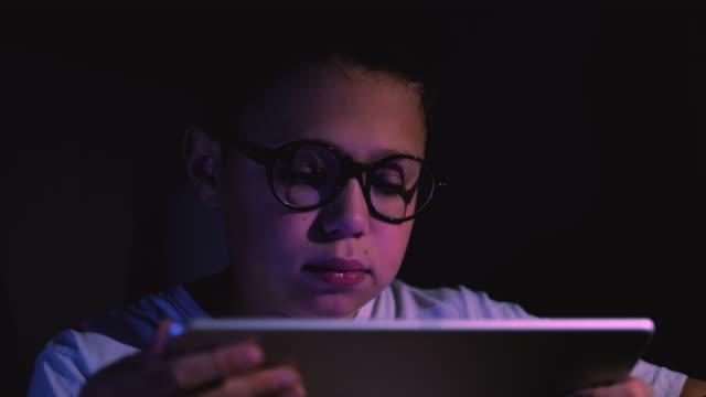 Lindo-niño-usando-tableta-en-la-habitación-oscura