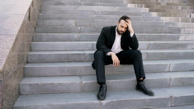 Verärgert-junge-Geschäftsmann-mit-Stress-und-sitzen-auf-Treppen-in-der-Straße-Geschäftsmann-mit-Deal-Probleme-Konzept