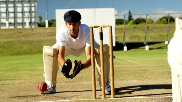 Encargado-del-Wicket-recoger-pelota-de-cricket-detrás-de-troncos-durante-partido