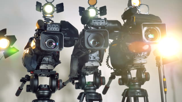 A-low-close-view-on-three-video-cameras-on-massive-stands-