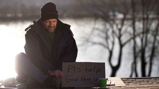 Hombre-pidiendo-dinero-con-signo-de-cartón