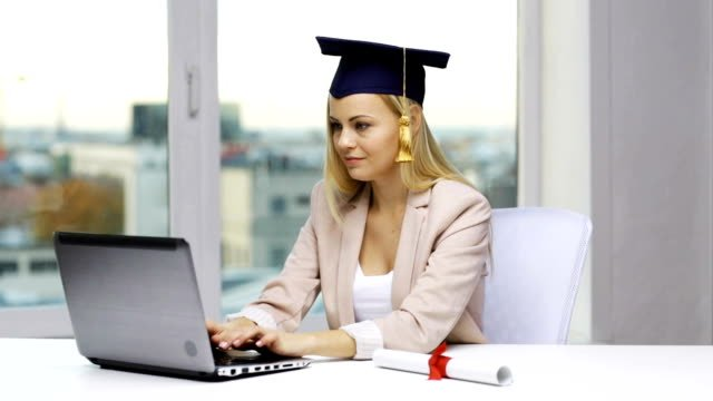 student-in-bachelor-cap-with-laptop-and-diploma