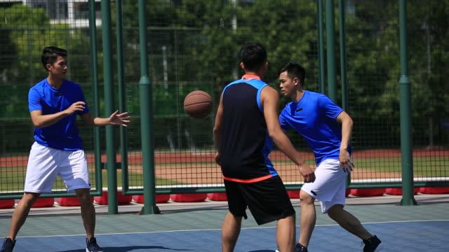 Junge-asiatische-Erwachsene-spielen-Basketball-im-freien