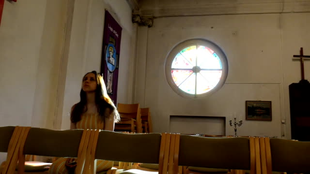 Young-caucasian-religious-devoted-woman-on-the-bench-in-Catholic-Church