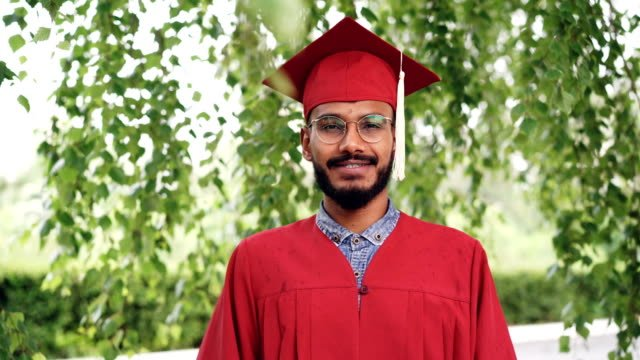 Portrait-of-bearded-mixed-race-man-graduating-student-in-gown-and-mortar-board-smiling-and-looking-at-camera-standing-outdoors-on-campus-People-and-education-concept-
