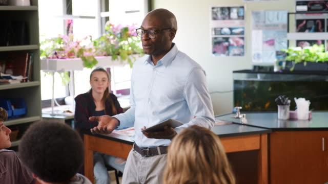Tutor-de-secundaria-hombre-con-tableta-Digital-enseñanza-estudiantes-en-clase-de-Biología