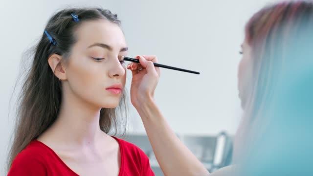 Close-up-Modell-Gesicht-während-der-Arbeitszeit-von-professionellen-weiblichen-Maskenbildner-Lidschatten-auftragen