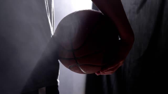 Aufnahmen-von-Basketball-Spieler-mit-Ball-im-nebligen-Dunkelkammer-stehen-in-der-Nähe