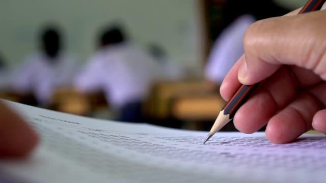 Prueba-de-concepto-de-educación:-estudiante-de-manos-con-pluma-para-exámenes-prueba-escribir-la-hoja-de-respuestas-o-el-ejercicio-para-la-toma-de-llenan-en-la-computadora-de-papel-carbón-de-examen-en-la-mesa-de-madera-en-el-salón-de-clases-en-la-escuel