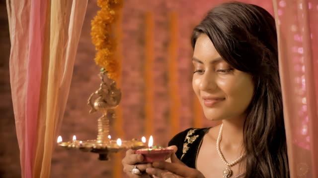 Una-hembra-de-buen-aspecto-en-una-luces-de-sari-colgar-lámpara-y-sonrisas-mirando-a-la-cámara-de-aceite