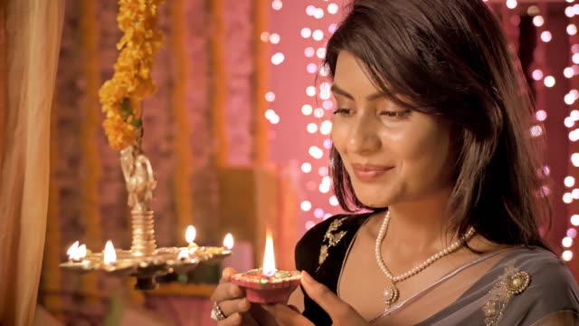 A-cerca-de-la-mujer-hermosa-y-tradicional-una-lámpara-de-iluminación-durante-el-festival-de-Diwali-