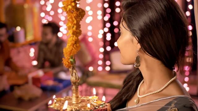 mujer-tradicional-de-iluminación-de-una-lámpara-de-aceite-durante-el-festival-de-Diwali-y-miembros-de-su-familia-hablando-en-el-fondo-