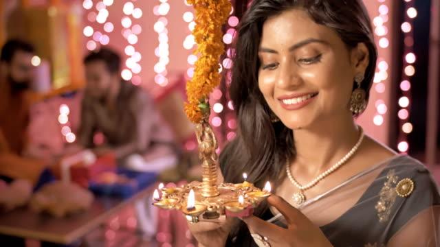Una-hermosa-mujer-sosteniendo-una-lámpara-de-aceite-tierra-en-sonrisas-de-manos-mientras-sus-amigos-en-el-tradicional