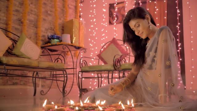 Una-mujer-atractiva-y-sonriente-sentada-en-el-suelo-en-un-tradicional-sari-y-dibujo-un-Rangoli