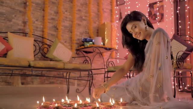 Una-señora-sonriente-dibujando-Rangoli-(forma-de-arte)-en-el-piso-con-pétalos-de-flores-de-color-arena-y-aceite-de-las-lámparas-(diyas)
