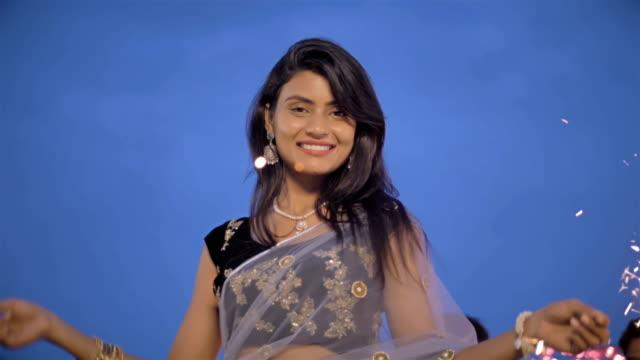 Tiro-de-cámara-lenta-de-una-señora-atractiva-y-sonriente-jugando-con-fuegos-artificiales-al-aire-libre-durante-el-Festival-de-Diwali