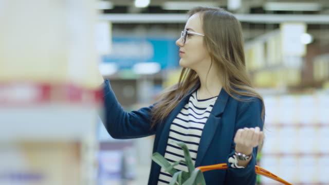 En-el-supermercado:-hermosa-joven-navega-a-través-de-la-sección-de-enlatados-de-la-tienda-Tiene-cesta-llena-de-alimentos-saludables-