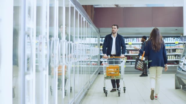 At-the-Supermarket:-Handsome-Man-Pushes-Shopping-Card-and-Browses-for-Products-in-the-Frozen-Goods-Section-Man-Looks-into-Glass-Door-Fridge-Choosing-Dairy-Products-Other-Customer-Shopping-