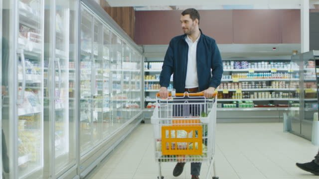 At-the-Supermarket:-Handsome-Man-Pushes-Shopping-Card-and-Browses-for-Products-in-the-Frozen-Goods-Section-Other-Customer-in-the-Background-