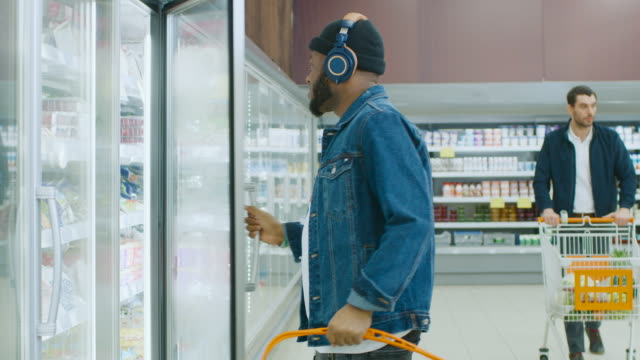 At-the-Supermarket:-Stylish-African-American-Guy-with-Headphones-Chooses-Products-in-the-Frozen-Goods-From-the-Fridge-and-Puts-them-into-Shopping-Basket-Slow-Motion-