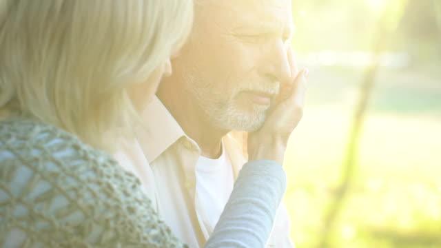 Alte-Frau-unterstützen-und-umarmt-ihr-krank-schreienden-Mann-schlechte-Nachrichten-Verzweiflung